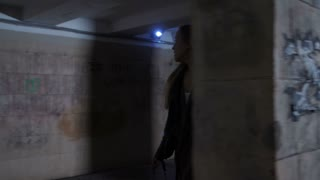 Scared young female trying to walk away from stranger at night in dark underpass subway. Female walking behind tunnel columns looking back afraid of the man following her in darkness. Steadicam