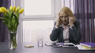 Senior attractive business woman working on touchpad suffering from headache in office. Exhausted female worker sitting at table, touching temples and tired eyes, taking painkiller medicine. Dolly