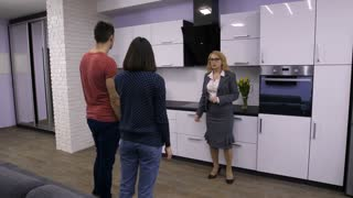 Senior attractive female real-estate agent showing new modern apartment interior to young family couple. Young adults walking and talking to realtor in their new house. Steadicam shot.