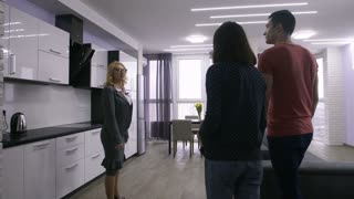 Senior attractive female real-estate agent showing new modern apartment interior to young family couple. Young excited adults walking and talking to realtor in their new house. Steadicam shot.