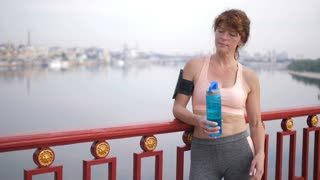 Senior female athlete with red hair standing on city bridge, resting after intense workout and jogging. Active redhead woman opening sport bottle and drinking water on cityscape background