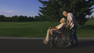 Senior handsome bearded man pushing wife in wheelchair while taking a walk in countryside. Positive beautiful senior couple with white hair enjoying and having fun together outdoors. Steadicam