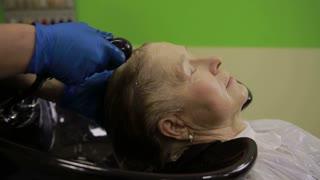 Senior woman enjoying hair washing in salon