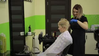Senior woman having her hair dyed by beautician