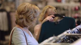 Senior women choosing dress while shopping in shop
