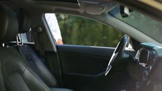 Serious businessman fastening seat belt in car