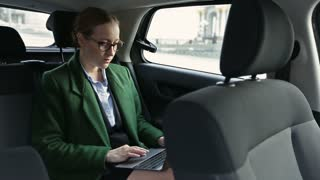 Serious businesswoman working in car on laptop