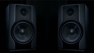Set of two black round audio speakers vibrating from sound of loud music on low frequency. Modern sub-woofers on black background.