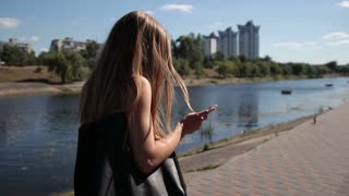 Shocked woman droping smartphone on stone sidewalk