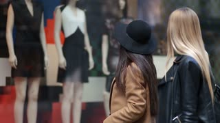 Shopping women looking at clothing store window