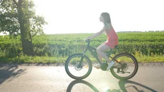 Side full length view of beautiful teenage girl biking through fields during sunset in summer. Schoolgirl enjoying summer holidays while riding bike in countryside. Sun flare through trees. Steadicam