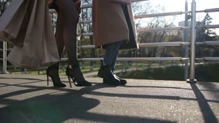 Side view of females legs walking on bridge