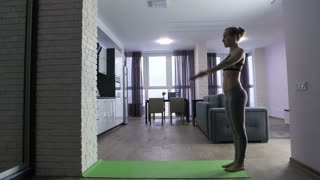 Side view slow motion shot of young fit woman in sportswear doing handstand near the wall in domestic room. Morning workout routine of healthy female doing exercises on mat at home
