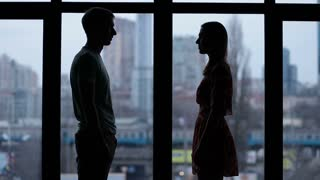 Silhouette of couple holding hands by window