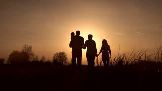 Silhouettes of grandparents with kids at sunset