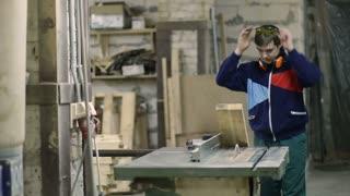 Skilled carpenter cutting wood using circular saw