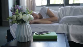 Sleepy woman turning off mobile alarm clock