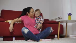 Slow motion of beautiful adult mother sitting near sofa indoors with her cute baby son blowing bubbles and talking to her child. Baby in striped outfit looking at bubbles learning new things. Dolly