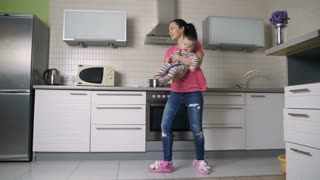 Slow motion of beautiful hispanic woman holding her baby son in her arms, playing and dancing with him in kitchen at home. Housewife having fun with child while cooking dinner for family. Dolly shot