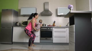 Slow motion of cheerful young latin mother doing squats while holding her infant child. Slim attractive fitness woman training together with her baby in the kitchen. Dolly shot.