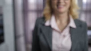 Slow motion of female's midsection in formal jacket holding house keys in hand and showing to camera. Real-estate agent offering home keys to clients at table. Keys with wooden house shaped key ring.