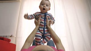 Slow motion of happy baby boy's portrait. Mother's hands lifting her child up in the air, playing and enjoying with her cheerful sweet laughing infant child. Low angle view shot