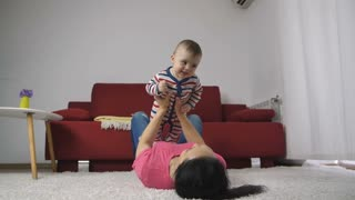 Slow motion of happy laughing baby boy and his mother playing together at home. Mother lying on the carpet near the couch and lifting her smiling newborn baby son into the air.