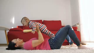 Slow motion of middle-aged attractive mother having fun with her baby son at home near the sofa holding and lifting him up. Sweet little infant laughing, smiling and enjoying with mom. Dolly shot