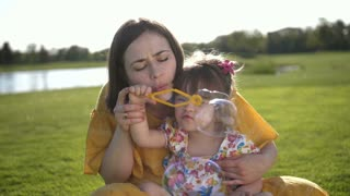 Slow motion of mother sitting on green grass meadow with sweet little toddler daughter with down syndrome and blowing soap bubbles together. Happy family spending leisure together in summer nature