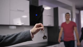 Slow motion of realtor's hand holding house keys and young smiling couple approaching real-estate agent and taking keys. Happy married woman and man embracing and thanking for newly purchased house.