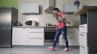 Slow motion of young beautiful fit mother entertaining her laughing infant child by swinging him in her arms in the kitchen. Happy mother and baby son enjoying and having fun at home. Dolly shot