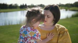 Slow motion portrait of young mother holding cute little toddler daughter with down syndrom. Beautiful family of mom and special needs girl kissing and laughing together in summer park on green meadow