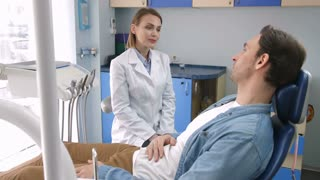 Smiling friendly oral health doctor in white lab coat sitting near young male patient in dental clinic and telling him about treatment plan. Oral health doctor talking with client