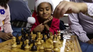 Smiling girl in santa hat watching chess game