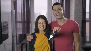 Smiling happy young adults couple holding keys to their new house and showing it to the camera indoors. Excited sweet family became owners of their new home. Keys with wooden house shaped key ring.