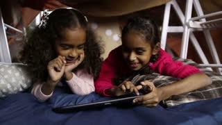 Smiling little girls working on digital tablet