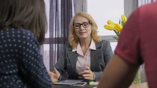 Smiling senior adult financial consultant talking to clients in office at the table. Friendly mature blonde hair female expert advisor in eyeglasses consulting on financial matters to couple.