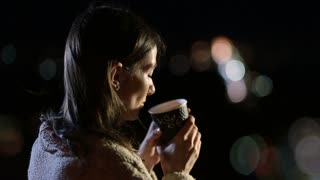 Smiling woman drinking coffee outdoors at night