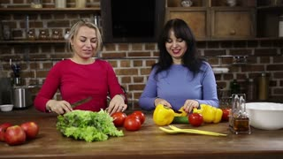 Smiling women cutting vegetables in the kitchen