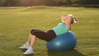 Sportswoman doing abdominal crunches on fit ball