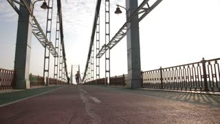 Sporty athletic senior redhead woman running on bridge in city, then stops to relax and catch breath. Happy smiling fit female satisfied with her workout at sunrise. Steadicam stabilized shot
