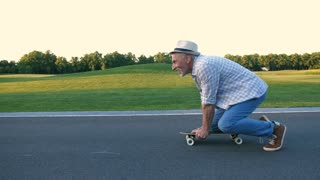 Steadicam shot of active handsome bearded man in hat learning to keep balance on skateboard. Positive cheerful aged male young in heart skateboarding on knee on countryside road in summer. Side view