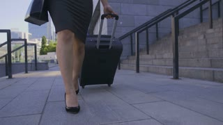 Steadicam shot of business woman's legs in heels walking at the airport with suitcase. Young asian executive arrived for business meeting and walking in business city area