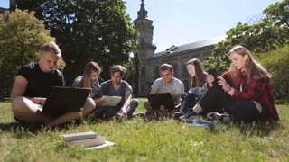 Students studying with laptop and tablet on grass