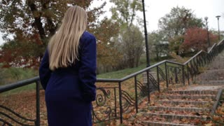Stunning woman climbing staircase in autumn park