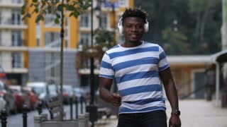 Stylish african american man in headphones enjoying afrohouse music and dancing against urbanscape backgound. Trendy black guy listening to the sound of afrobeat and making dance moves on city street.