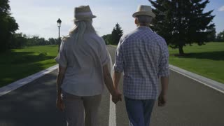 Stylish senior couple with gray hair and in hats talking a walk on road in beautiful green park. Positive married wife and husband holding hands, embracing and changing hats. Happy retirement
