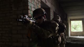 Subdivision of anti-terrorist police during tactical exercises entering the premises. Group of soldiers carrying guns preparing for help hostage in abandoned building during anti terrorism operation.
