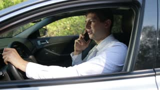 Succesful bussinessman talking on phone in car