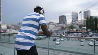 Surprised handsome african american man in earphones reading message on smart phone over cityscape background. Positive black male hipster checking email on mobile phone while relaxing in city. Slo mo